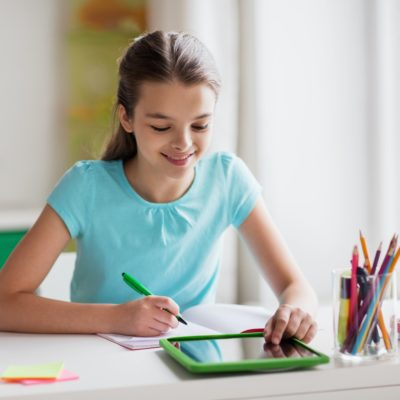 Scriblr - girl with tablet pc writing to notebook at home 1 400x400